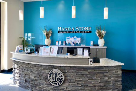 Hand & Stone Massage & Facial Spa Stone Reception Desk with Blue Wal
